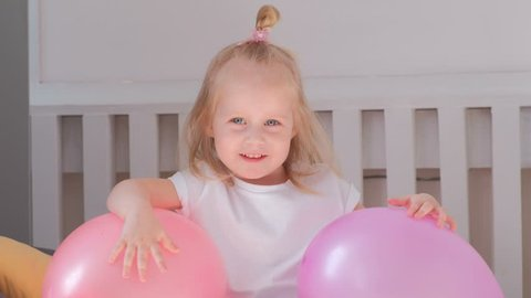 Little charming blond girl sitting on bed in her room with pink balloons and smiling. Portrait.