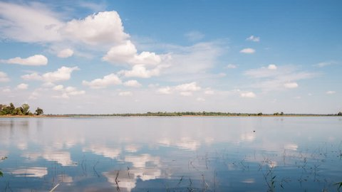 Time lapse of River lake landscape reflection clouds sky moving in summer