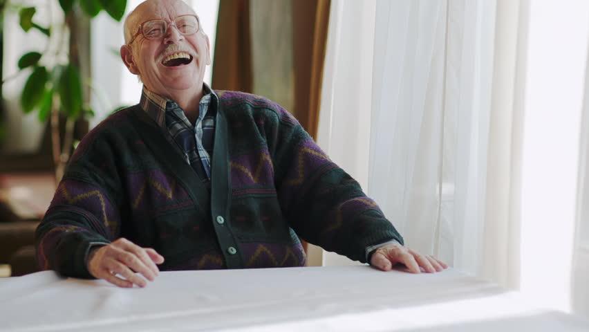 Video clip of senior man sat at table lift head backwards and laughing.