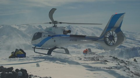 The helicopter left skiers on the slope of the mountain and flew raising a cloud of snow