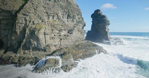 Aerial Over wild ocean surf on rocks at Piha, Auckland, New Zealand