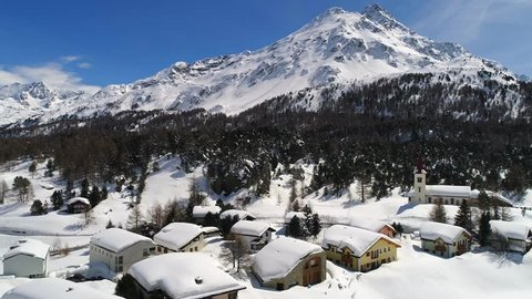 Little village and forest covered with snow. Engadine Valley in the Swiss Alps. Aerial view