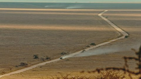 Cinematic shot of safari car driving through lush, vast, dusty landscape fields of Serengeti National Park, Tanzania, Africa with wildebeest and antelope herds grazing