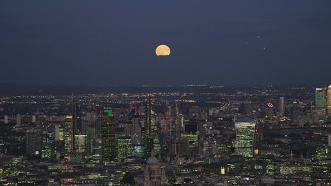 Aerial view at night moon rising over London cityscape financial district skyscrapers Canary Wharf River Thames England UK RED WEAPON