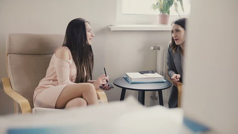 Two beautiful European women sit and talk informally. Interview for office position. Business coach training session 4K
