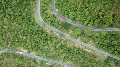 Top view. Aerial view road pass and forest from drone. Royalty high-quality free stock video footage of road in forest. Road in forest is beautiful with many tree, road on pass very winding and curve