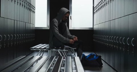 A beautiful fit young woman (girl) with a gray hooded sweatshirt in the gym's locker room, getting ready to train