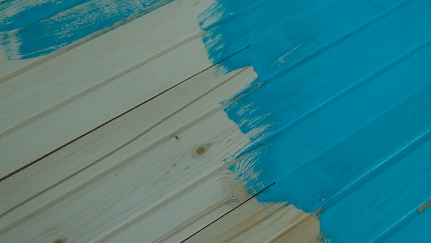 Painter drives his brush along a wooden board with blue paint in slow motion, top view | Shutterstock HD Video #1009782725