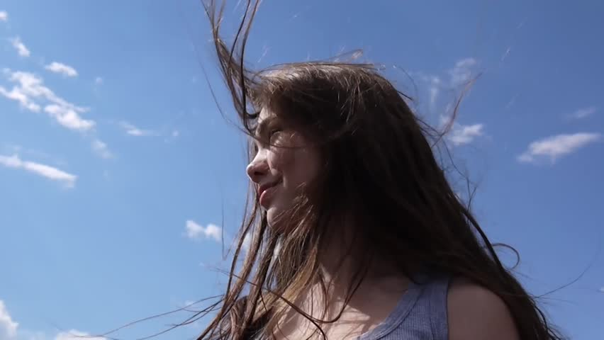 Close up portrait of beautiful young girl with blowing hair in wind