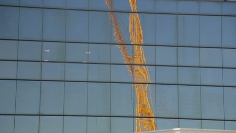 Two Yellow Construction Cranes Reflected in Mirror Window of Building