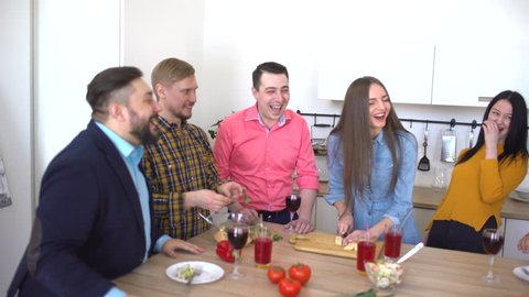 Young people girls guys cooking dinner   in kitchen preparing food together for party. Group of friends talking having fun laughing meeting . Students college teenagers. friendship happy holiday 4 k