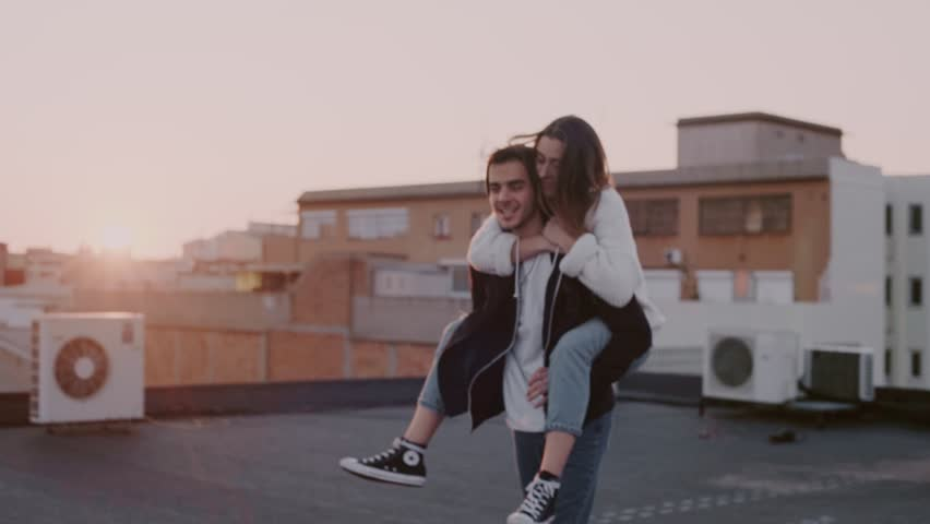 Young couple in love fools around and has fun on rooftop at sunset, laugh and smile, kiss each other fondly with beautiful sunlight leaks, piggy ride teenager relationship emotions, blogger lifestyle