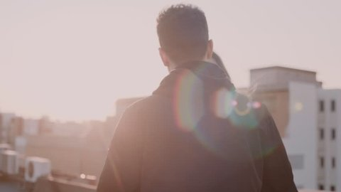 Slow motion shot of young beautiful sensual woman or millennial girl, hug her boyfriend or partner and look in camera with emotions and feelings, in amazing sunset light on rooftop
