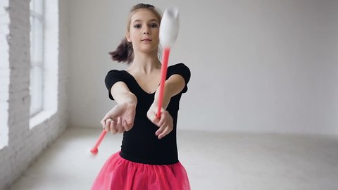 Rhythmic beautiful gymnast holding maces it makes acrobatic movements on white background in gymnastic hall. Girl dressed in black body and pink skirt. Slow motion, slow