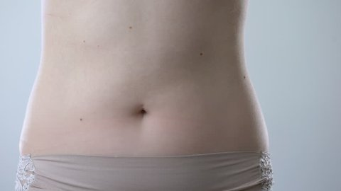 Surgeon drawing marks on abdomen, preparing woman for liposuction surgery