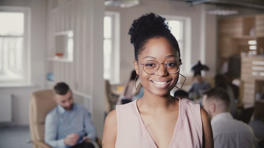 Portrait of beautiful young African American successful businesswoman, looking at camera in loft office background 4K. | Shutterstock HD Video #1009815845