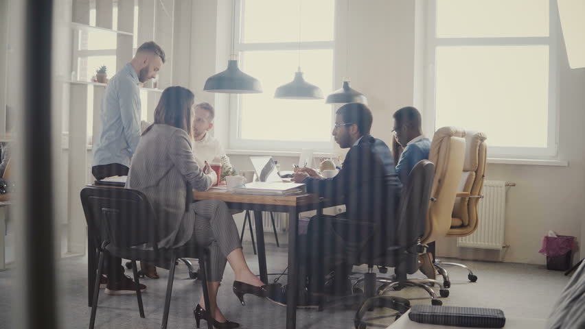 Dolly shot of teamwork at loft modern office table. Multiethnic business people cooperate, discuss market at meeting 4K. | Shutterstock HD Video #1009818305