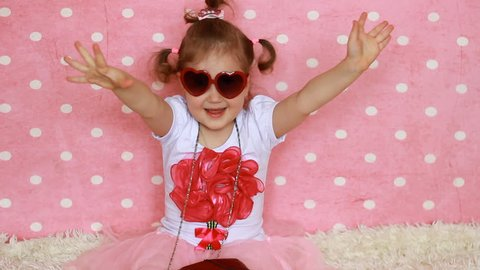 Sunglasses in the shape of heart. A little girl lady dresses up - red bag and shoes. Funny child. Pink background. Glamour. Fashion. Fashionista.