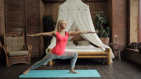 Fitness lady performs yoga asanas in bedroom at home. Middle aged woman is practicing yoga actively on floor indoors. Attractive blonde with tail is standing on rug sideways with raised hands then