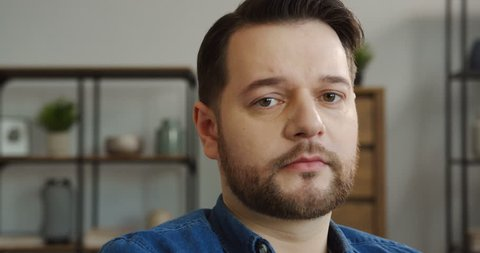 Portrait shot of the Caucasian middle aged serious man in the blue jeans shirt looking at the camera with a sad face in the nice living room. Indoor