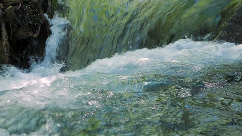 small waterfall creates a foam. Slow motion.