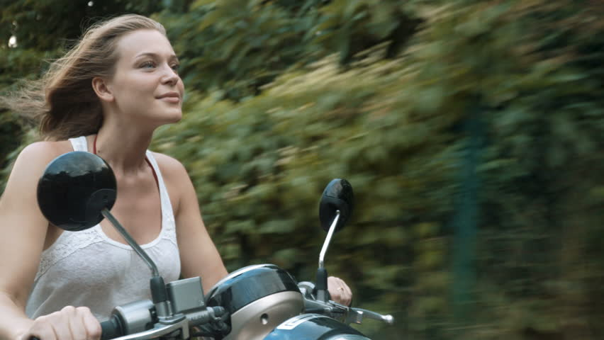 Young woman riding a scooter in the summertime | Shutterstock HD Video #1009842365