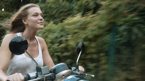 Young woman riding a scooter in the summertime