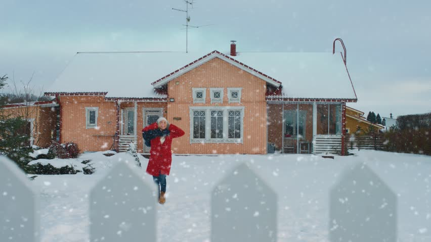 Beautiful Young Smiling Woman Jumps and Spins Under Falling Snow. Girl in a Red Coat with a Scarf Enjoys Winter Day in the Backyard. Idyllic House Standing in the Background. Shot on RED EPIC-W 8K