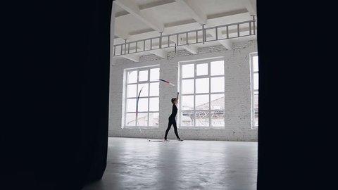 Rhythmic gymnastics: Girl in black body perform gymnastics exercise with a colored ribbon in sport school near big windows. Ballet School, slow motion