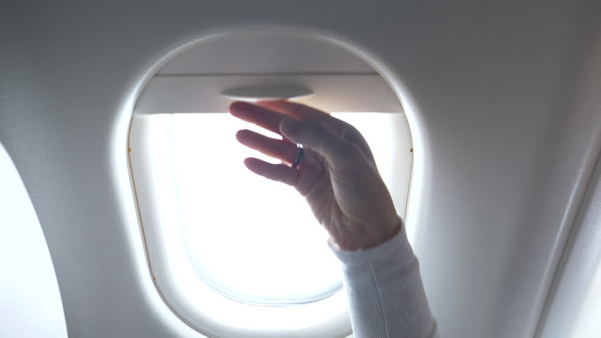 CLOSE UP: Young woman looks through the airplane window and closes the blinds. Female traveler on transatlantic flight watches the bright sky and the large airplane wing before closing the shades.
