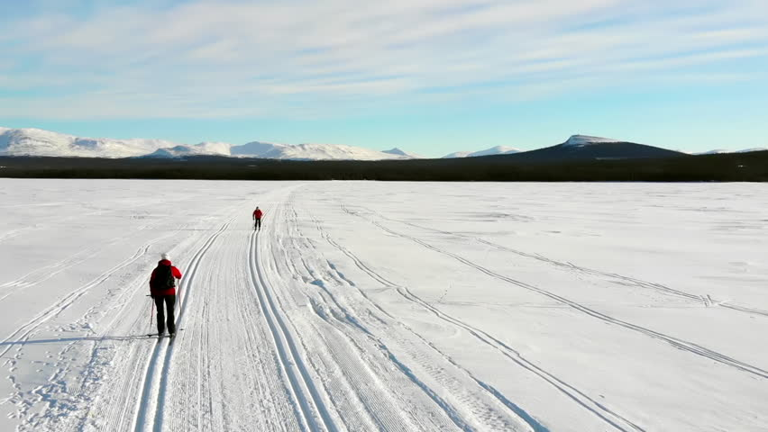 Two women cross country skiing on a lake in the Swedish mountains.