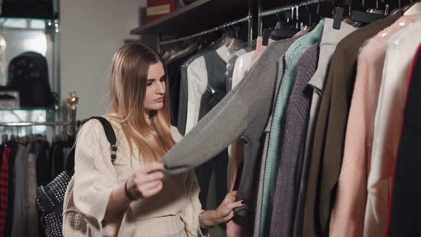 A young and pretty woman wants to buy clothes, the lady touches the jacket material, which weighs on the hanger, the shopaholic came in an expensive and representative boutique   Shutterstock HD Video #1009924625