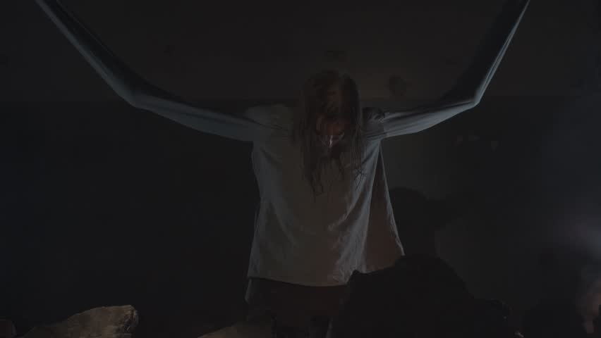 Crazy long haired caucasian man with straitjacket sleeves tied to ceiling in abandoned building