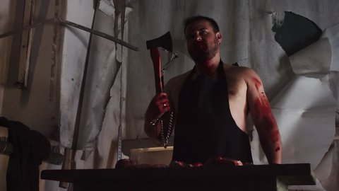 Maniac scary caucasian bearded buffed killer in apron covered in blood in abandoned building laughing and chop meat with axe on table