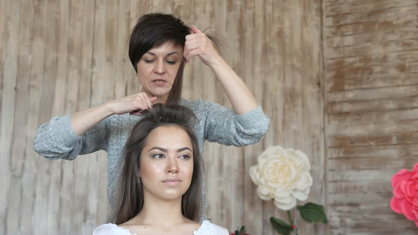 Makeup artist stylist works with model. hairdresser does the hair styling of the model. woman is working a styler with the girl's long hair. The hairdresser makes curls on the girl's straight hair. | Shutterstock HD Video #1009938125