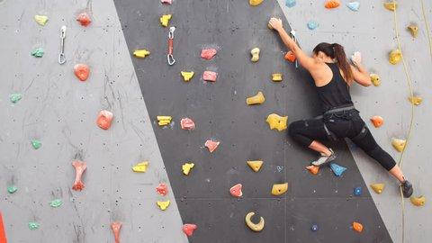 Women climbing on a wall in an outdoor climbing center.