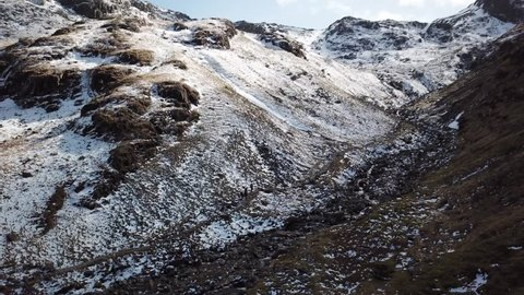 Aerial drone footage sweeping along a hiking trail towards Scafell Pike, the tallest mountain in England.  The barren rocky landscape is covered in snow and hikers make their way along the trail.