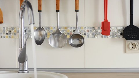 Tap is pouring water and kitchen utensils hang on the background of white ceramic tiles.