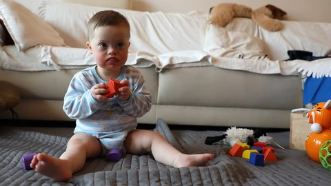 Cute baby boy with Down syndrome playing with toy