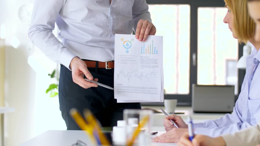 Business, corporate and people concept - businessman showing papers with charts to businesswomen at office meeting or presentation   Shutterstock HD Video #1009962695