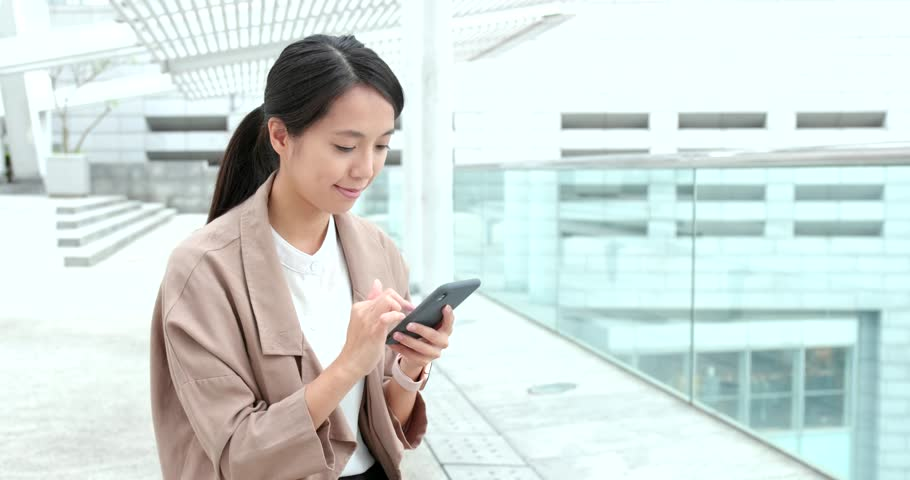 Woman work on mobile phone in city   Shutterstock HD Video #1009966265