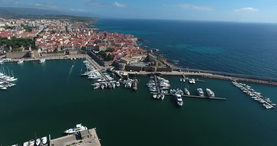 ALGHERO, SARDINIA, ITALY – JULY 2016 : Aerial shot over Alghero cityscape on a beautiful day with harbor and open sea in view