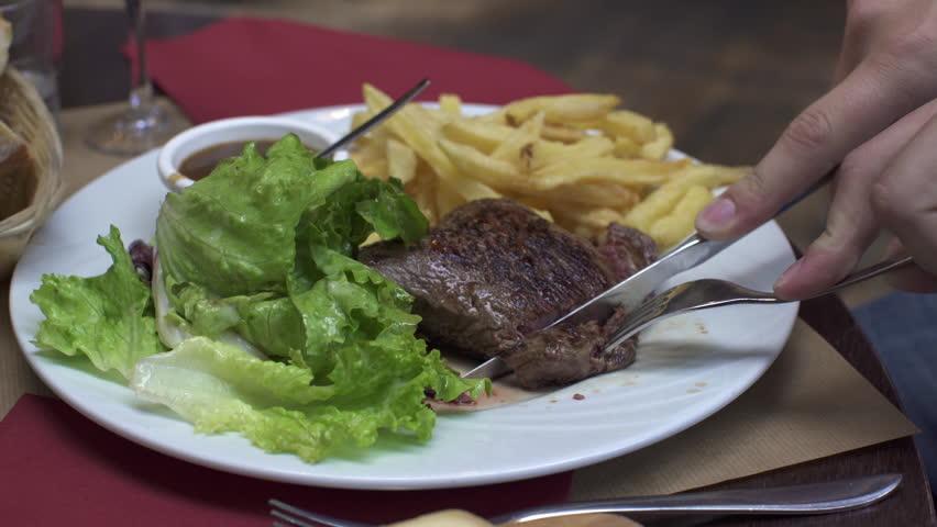 PARIS, FRANCE – SEPTEMBER 2016 : Video shot of cutting steak in a local french restaurant | Shutterstock HD Video #1009990715