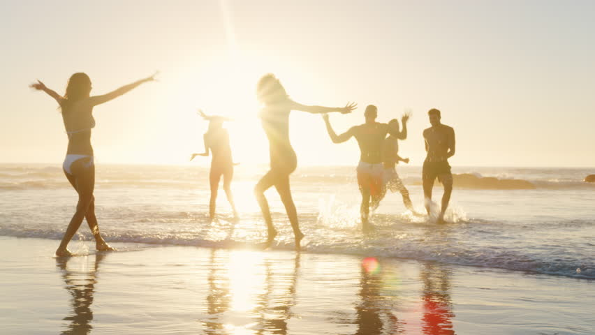 Group Of Friends Play In Waves At Sunset Together On Beach Vacation #1009994165