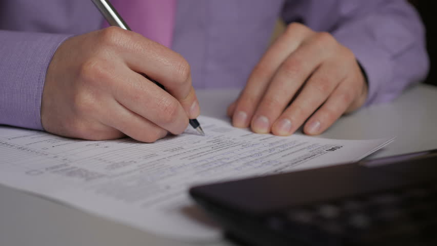 Man filling US tax form. tax form us business income office hand fill concept. Closeup.  Man Is Checking The Box Of Filing Status In The US Individual Income.  Tax Return Form 1040 | Shutterstock HD Video #1009997315