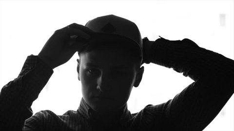 Young man putting on a baseball cap. Monochrome picture of a young man putting on baseball cap and then looking out the window. Slow motion, sketch, isolated.