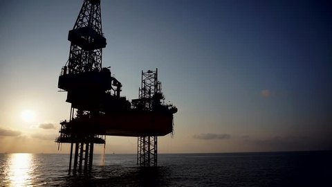 Oil and gas industry. View of silhouette tripod jack up drilling rig attached to wellhead platform during sunset in South China Sea.