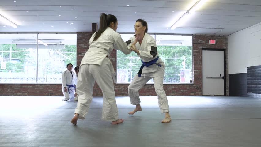 Young people practicing Jiu-jitsu in a dojo