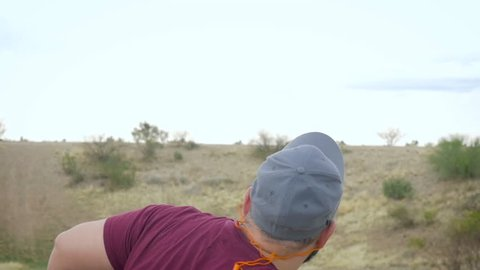 Young overweight man in a baseball hat throws a clay pigeon by hand in slow motion. Flying orange target explodes as a shotgun shell hits it. Medium shot represents target practice and sporting goods.