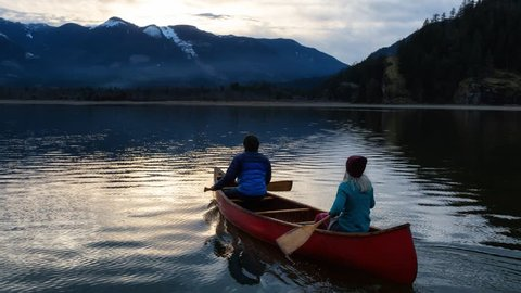 Cinemagraph picture animation of a couple friends on a wooden canoe enjoying the beautiful sunset. Taken in Harrison River, East of Vancouver, British Columbia, Canada. Continuous loop